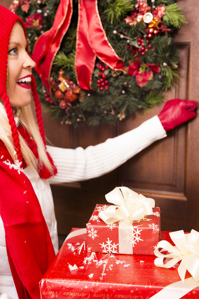 Woman knocks on front door to deliver Christmas gifts to a neighbor or family member.
