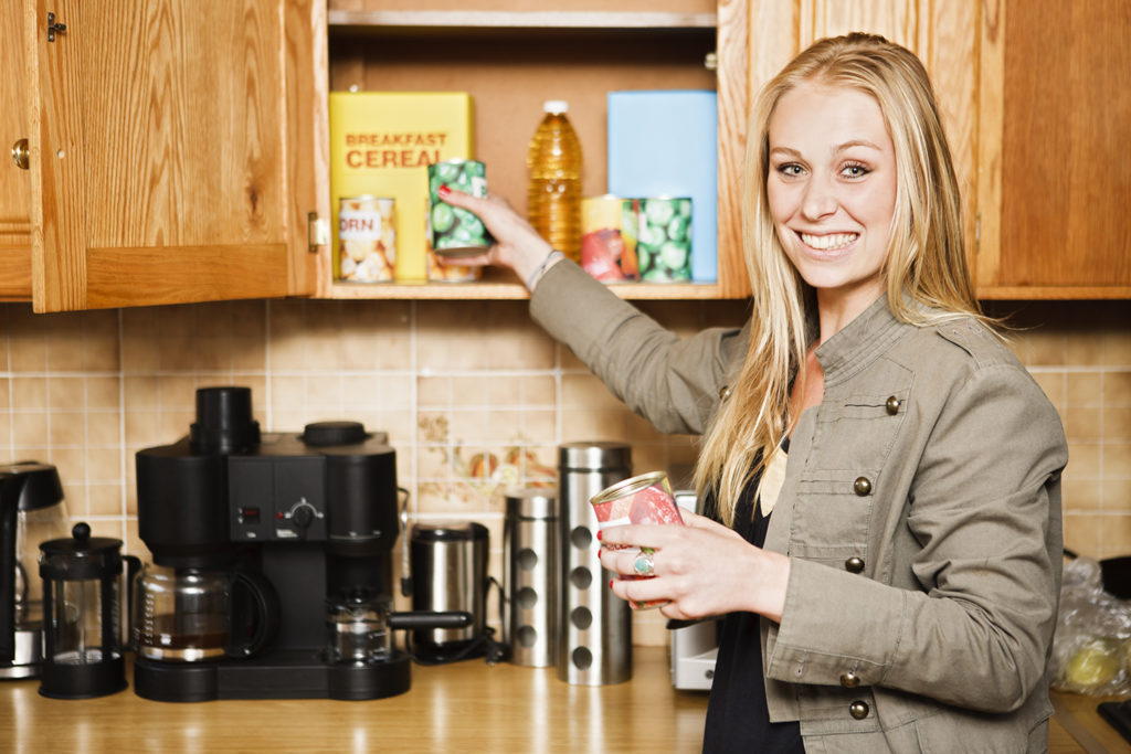 This pretty smiling blonde is either putting away canned food or reaching for it in her kitchen cabinets. The food labels are dummies made by the photographer.