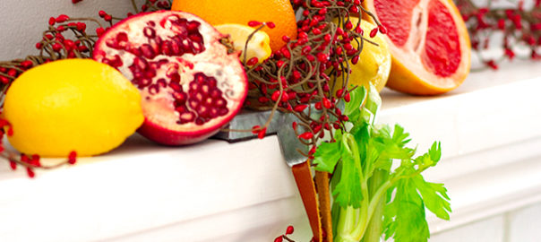 Lemon, orange, celery, pomegranate with holiday decor