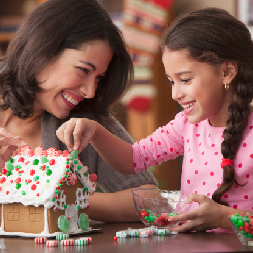 Mom and Daughter Assembling a Homemade Gingerbread House