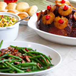 Holiday ham, green beans, and rolls table setting