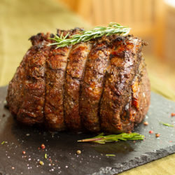 Prime rib garnished with rosemary and peppercorn