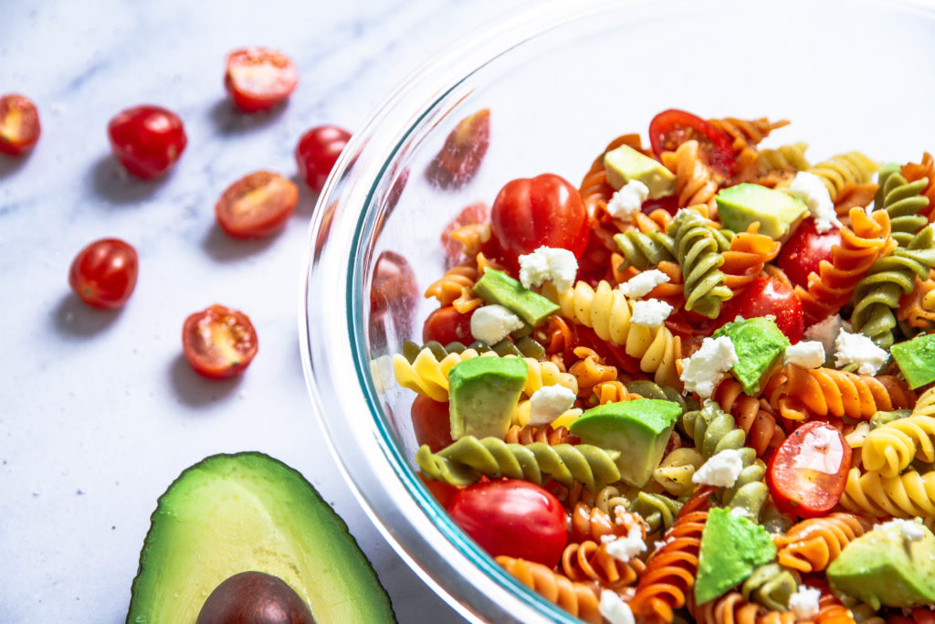 colorful veggie noodles with avocados, cherry tomatoes, and feta cheese in a glass bowl.