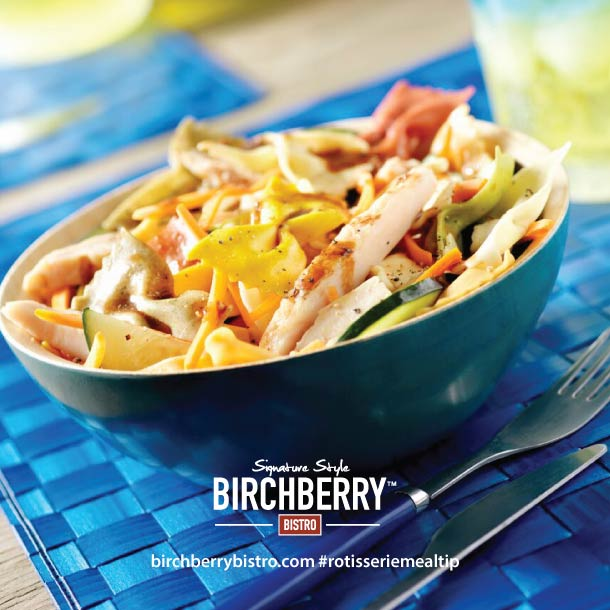 bowtie pasta chicken salad in a blue bowl on a place mat