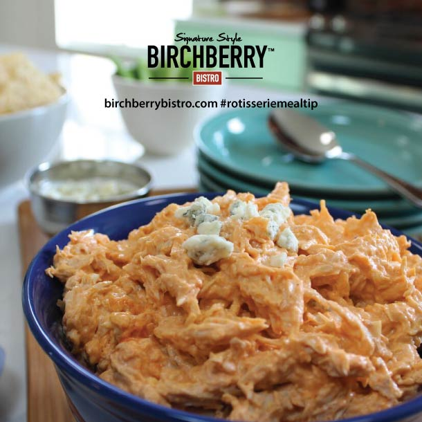 Shredded buffalo chicken dip in a blue bowl