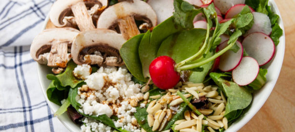 Spring green salad with radishes, slivered almonds, and mushrooms.