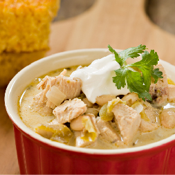 white chicken chili in a red bowl with sour cream on top