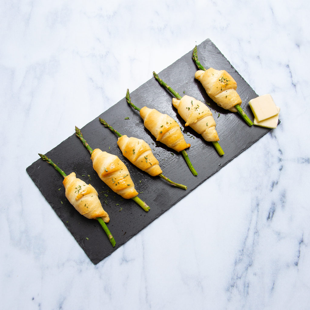 puff pastry wrapped asparagus with butter on a black slate and marble counter