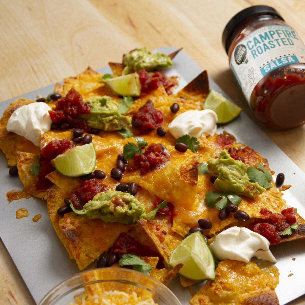 a silver sheet pan filled with nachos topped with cheese guacamole limes and sour cream