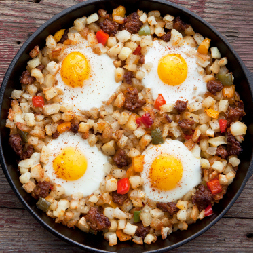 a skillet with cubed potatoes, tomatoes, meat and four eggs cracked on top