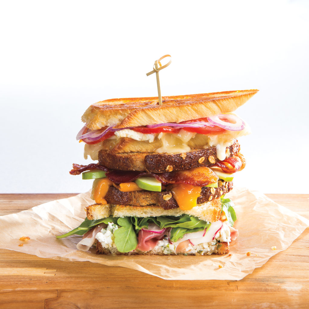 grilled cheese stack made of three different sandwiches on parchment paper