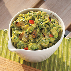 roasted guacamole with onions and tomatoes in a white bowl