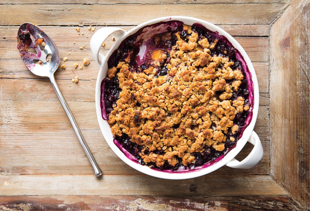 blueberry mango crisp with a spoon on the side on a light wood table setting