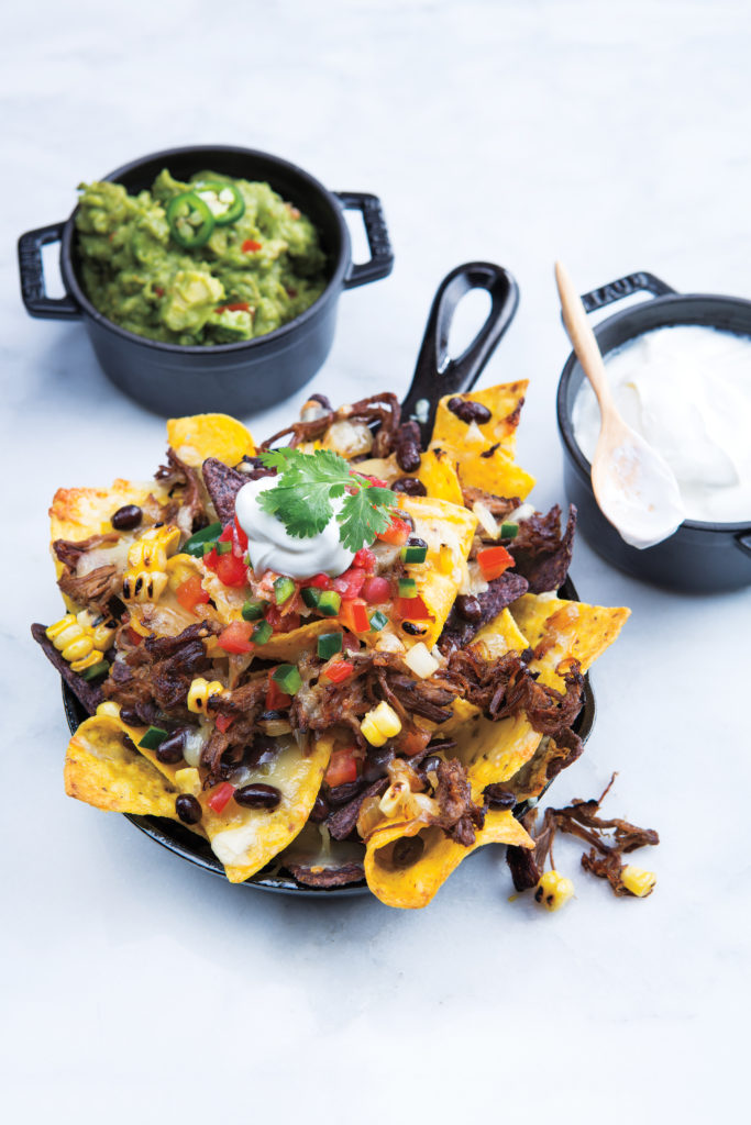 skillet nachos with a side of guacamole and sour cream