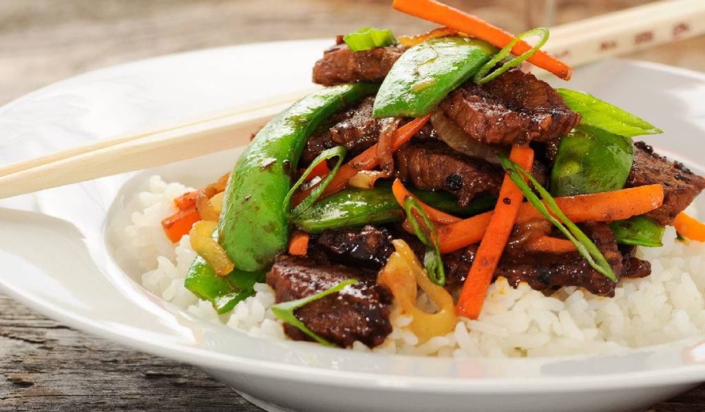 stir fry with snap pea and meat over rice in a white bowl