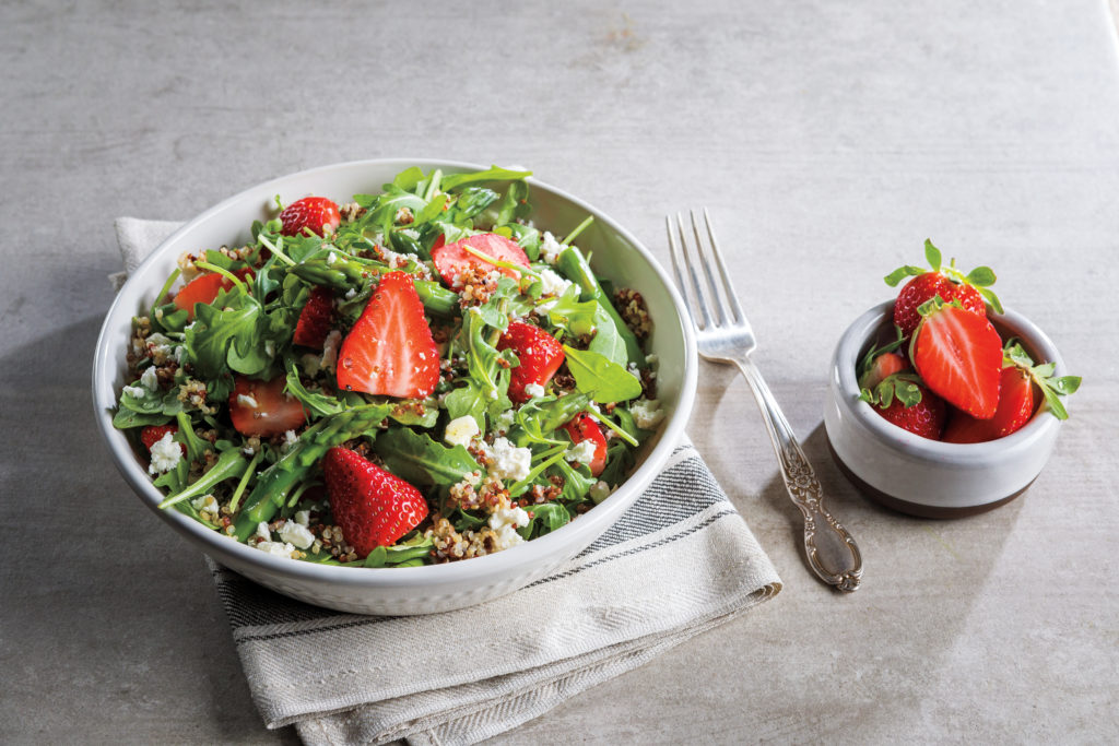 strawberry arugula and quinoa salad in a white bowl with a side bowl of fresh strawberries