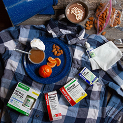 top shot of top care allergy medicine on a camping scene with a flannel shirt, hot chocolate, and snacks