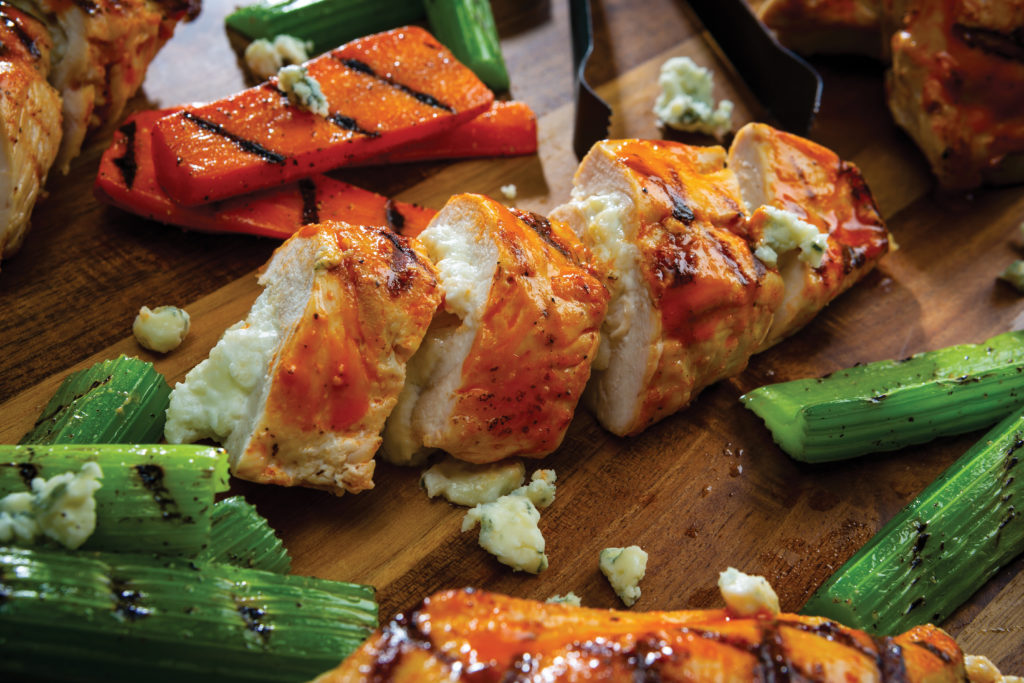 buffalo blue cheese stuffed chicken sliced with grilled carrots and celery