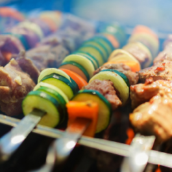 veggie and meat kabobs on a grill smoking