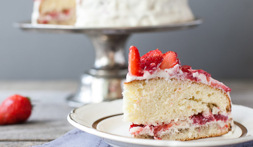 strawberry shortcake slice on a plate with a cake stand in the back