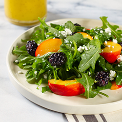 arugula salad with peaches blackberries and feta crumbles on a white plate