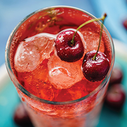 top view of a glass filled with shirley temple drink and cherries for garnish