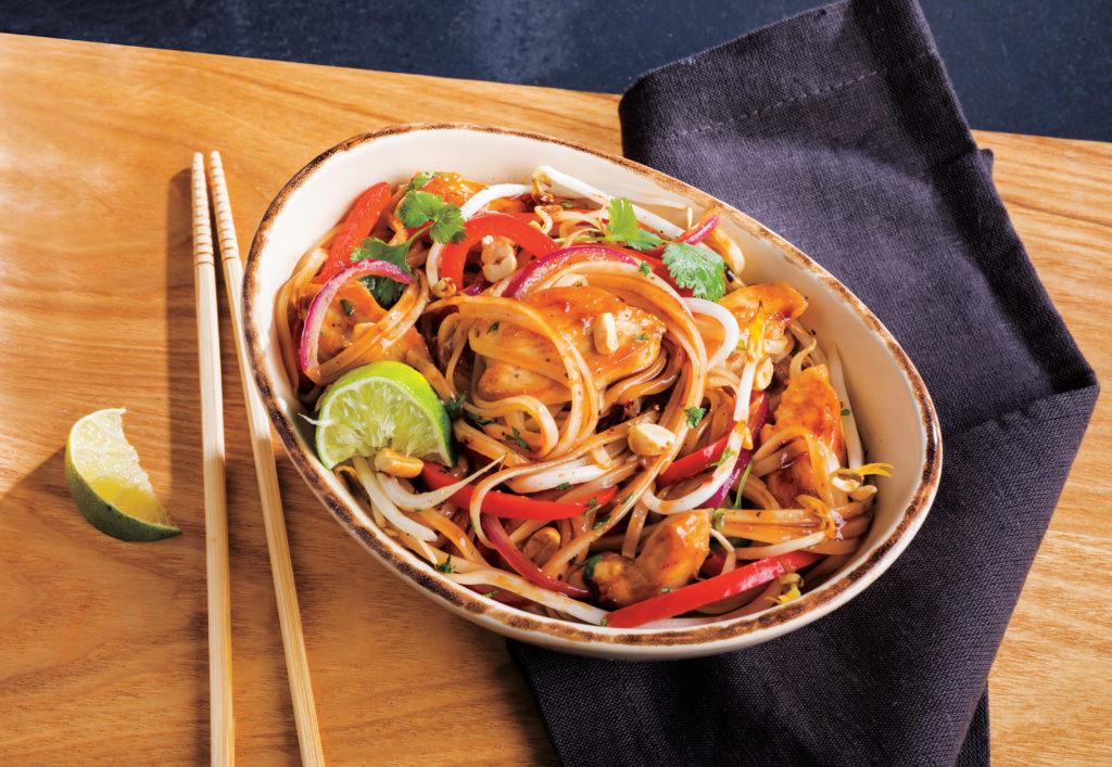 chicken pad thai in a bowl next to chopsticks