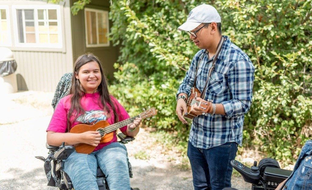 Child with neuromuscular disease playing the ukulele with a camp counselor.