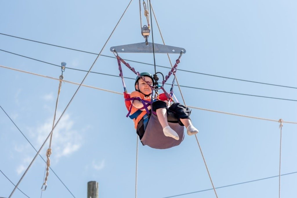 Child with neuromuscular disease on a swing.