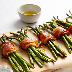 Cooked Asparagus Wrapped in Bacon with an Olive Oil Drizzle