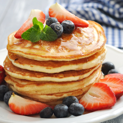 Stack of pancakes with strawberries, blueberries, and syrup drizzled on top