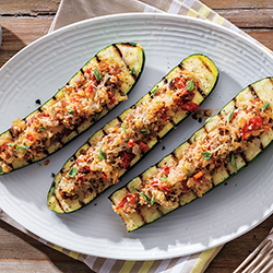 three grilled and stuffed zucchini boats on a white plate