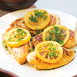 baked lemon chicken with parsley on a white plate