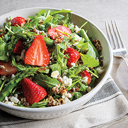 strawberry arugula and quinoa salad with asparagus in a bowl