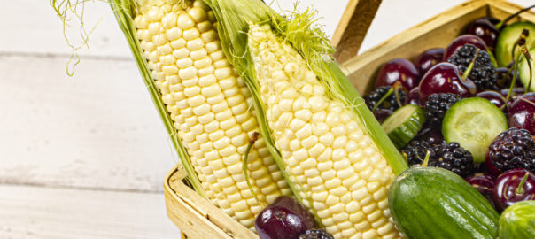 Corn, cherries, cucumbers and grapes in a basket